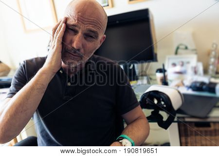 Adult man suffering from cyber sickness after using VR