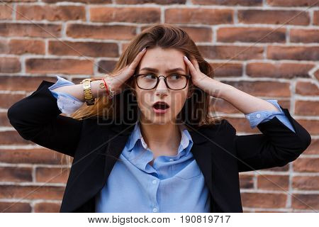 Frustrated business woman holding his hands to her head in frustration