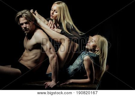 Love triangle. Polygamy and polyamory. Sexy man or macho with muscular body torso and two pretty girls or cute women stylish models with long blond hair on black background. Desire and seduction