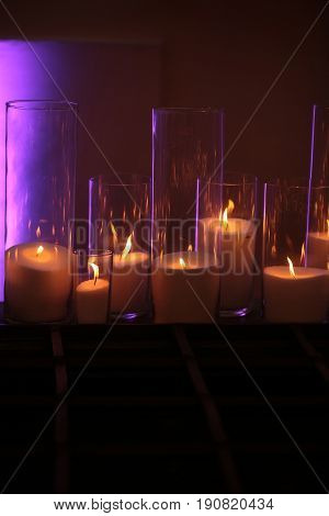 candles. Burning candles of white wax with flame reflection in elegant glass candleholders on wooden board on glowing background. Dark and light. Home decor. Holidays celebration. Heat energy