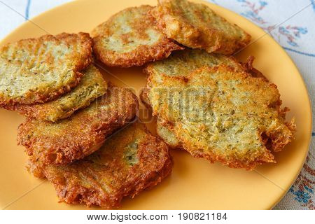 Fried pancakes with potato on orange plate