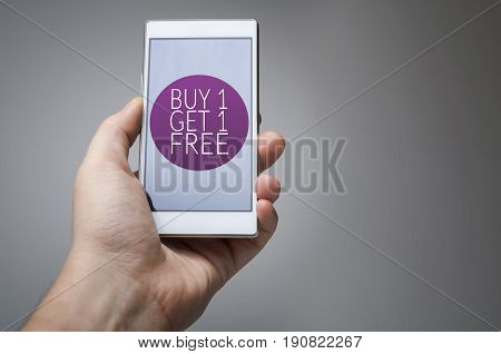 Buy one get one free icon on smart phone in hand on gray background