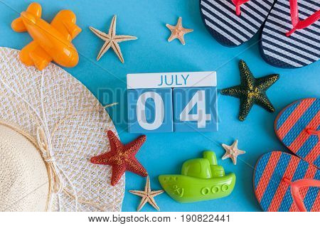 July 4th. Image of july 4 calendar with summer beach accessories and traveler outfit on background. Summer day, Vacation concept.