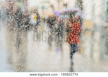 Abstract background of people hurrying down the city street in rainy day. Lonely Girl in red under umbrella. Intentional motion blur. Concept of seasons, weather, modern city.