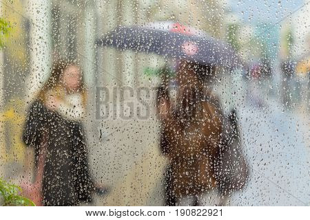 Abstract blurred silhouettes of people with umbrellas on a rainy day in the city, two girls seen through raindrops on window glass, blurred background, backdrop, wallpaper or banner design