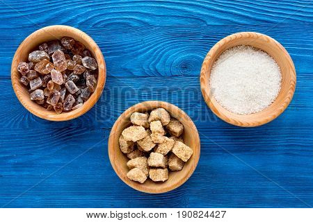 Lumps Of Sugar With Bowls Sweet Set On Blue Table Background Top View