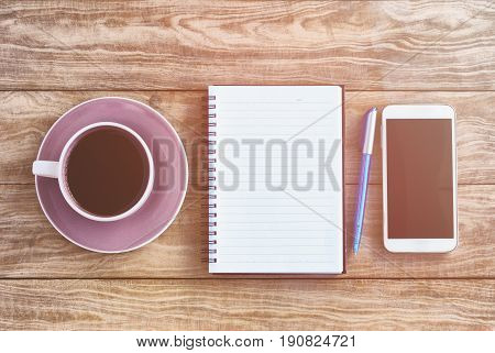 Top View Of Note Pad, Wood Table With Coffee, Pen And Smart Phone Retro Styled.