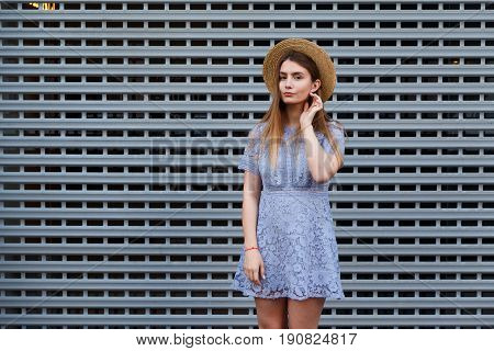 Portrait of a beautiful graceful woman in elegant hat and blue lace dress. Beauty, fashion concept.