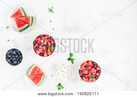 Watermelon salad and watermelon slices on white background. Top view flat lay