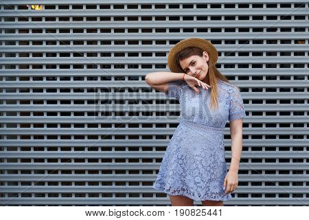Portrait of a beautiful graceful woman in elegant hat and blue lace dress. Beauty, fashion concept