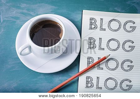 Blog blog blog- blogging concept on a notebook with cup of espresso coffee