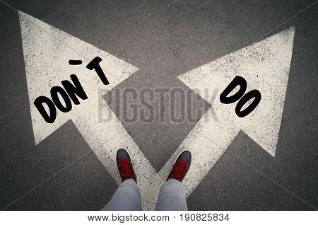DO versus DON`T written on the white arrows dilemmas concept.