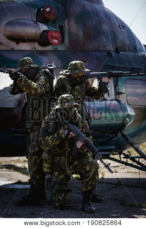 Photos of a group of military men with a gun in front of a helicopter