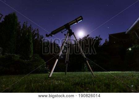 A telescope standing at backyard with night sky in the background. Astronomy and stars observing concept