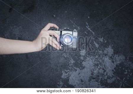 Male hand holding retro photo camera on the gray wall background