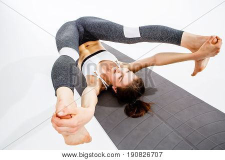 Girl doing twine lying on rug at blank background