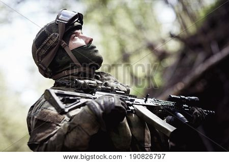 Photo of soldier in helmet at woods during day