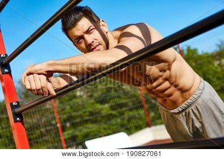 Outdoor portrait of mail bodybuilder, sunlit, looking away.