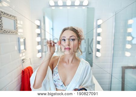 Beautiful young woman applying makeup at home in bathroom mirror.