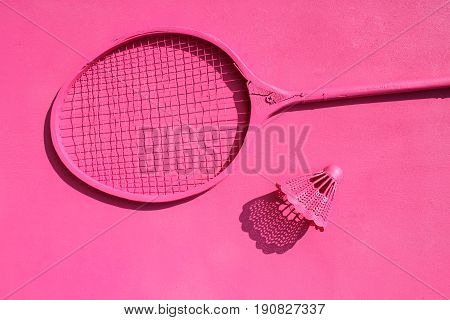 Bright pink background with a badminton racket and a shuttlecock