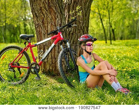Girl traveling bicycle in summer park. Bicyclist has rest near bike. Cycling is good for health in summer and spring. Girl is waiting for guy on date.