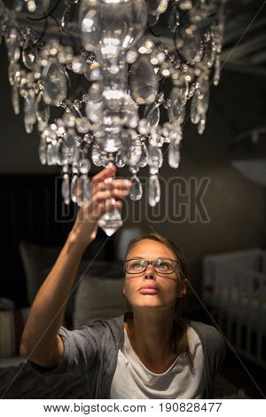 Pretty, young woman choosing the right chandelier for her appartment in a modern home furnishings store (color toned image; shallow DOF)
