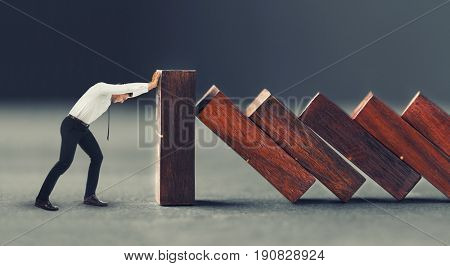 Man trying to stop falling huge dominoes on gray background. Leadership concept