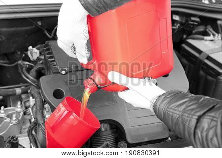 Male hands pouring engine oil from canister, closeup