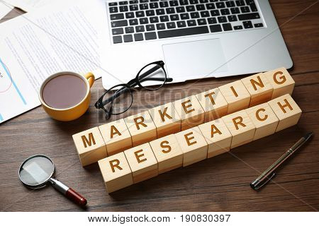 Wooden cubes with text MARKETING RESEARCH and laptop on table