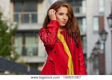 Portrait of beautiful brunette girl walking the street . Smiling. Urban city scene. Warm sunny weather. Outdoors