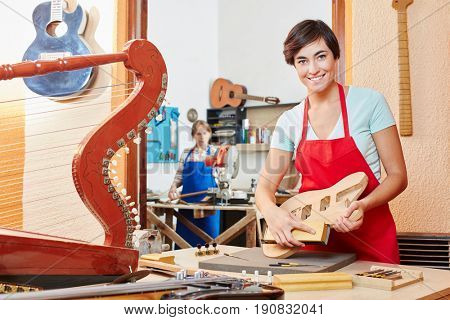 Woman in luthier's apprenticeship works on new guitar