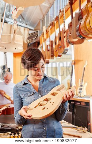 Woman as luthier making new guitar at carpenter's shop