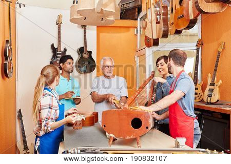 Guitar making at luthier's workshop with artisan's team