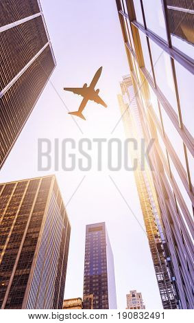 plane flying over modern office buildings in the sun, Manhattan financial district, New York City