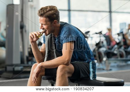 Sweaty young man eating energy bar at gym. Handsome mid guy enjoying chocolate after a heavy workout in fitness studio. Fit man biting a snack and resting on bench.