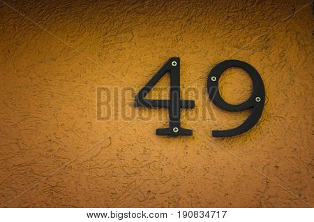 House number forty nine (49) on orange concrete wall
