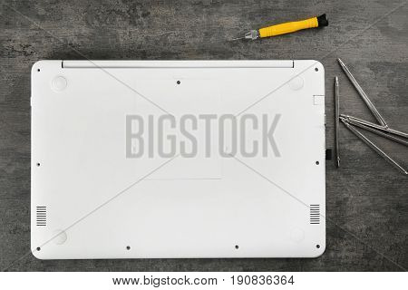 Assembled laptop body and screwdriver on grey table. Concept of computer repair