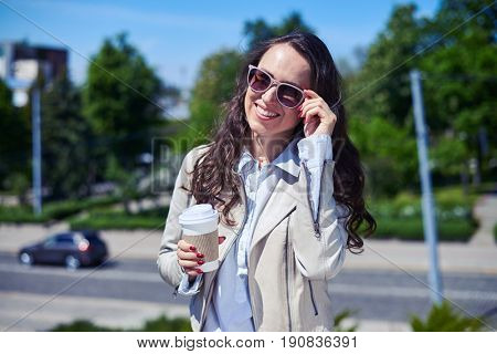 Mid shot of beautiful lade smiling and drinking coffee on top of building