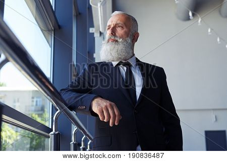 Low angle of concentrated gentleman with grey beard looking out window