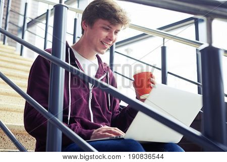 Mid shot of pleased male holding cup of coffee and chatting in laptop while sitting on stairs with copy space