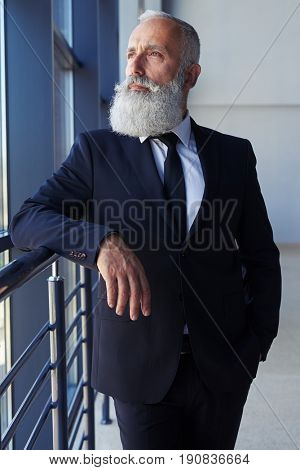 Vertical of thoughtful man with grey beard looking out window