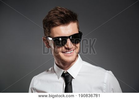 Image of cheerful young man dressed in formalwear wearing sunglasses standing isolated over grey wall. Looking aside.