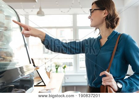 Smiling confident woman standing at a showcase in a cafeteria and choosing food