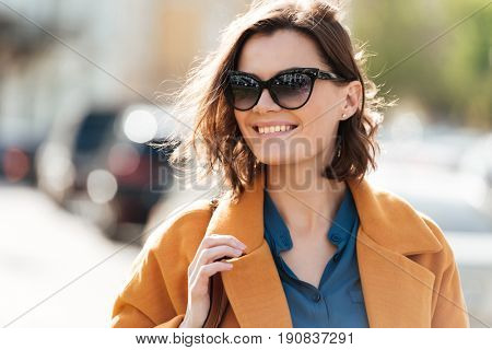 Close up portrait of a smiling young woman in sunglasses and coat walking on a city street