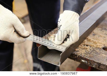 Man measuring off metal bar in workshop