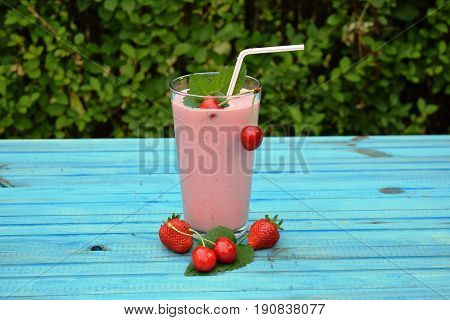 glass of strawberries, cherries smoothie with straw on wooden table. Protein cocktail. Healthy drink. Fresh homemade smoothie. Healthy breakfast of smoothie,