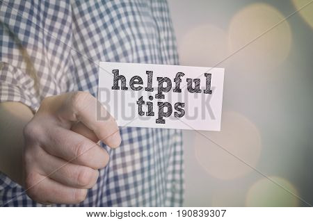 Helpful tips card in hand whith bokeh lights background