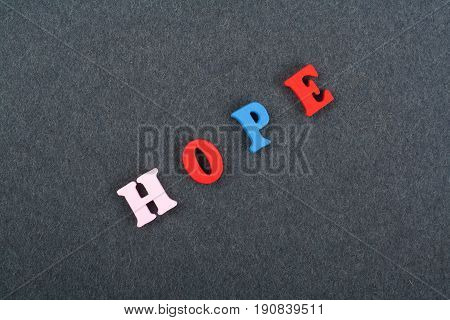 HOPE word on black board background composed from colorful abc alphabet block wooden letters, copy space for ad text. Learning english concept