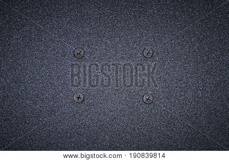 Sandpaper texture background. Black rough sandpaper sheet with screws close up.