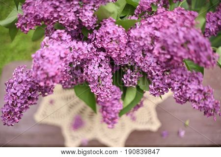 blurry lilac bouquet on knitted tissue  in crystal vase close up photo
